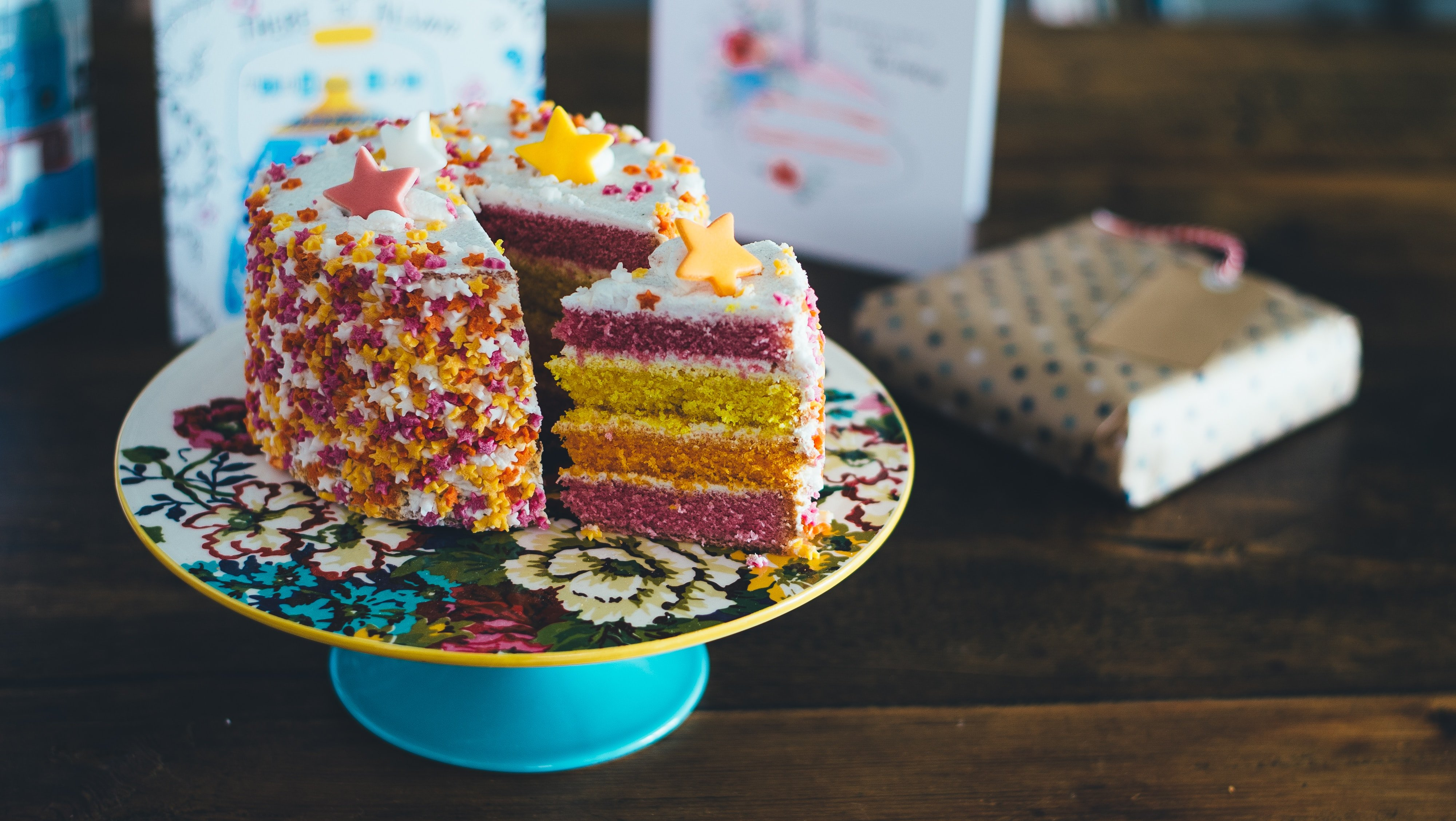 Layer cake of gratitude, rainbow flavors of cake on a blue cake pedestal